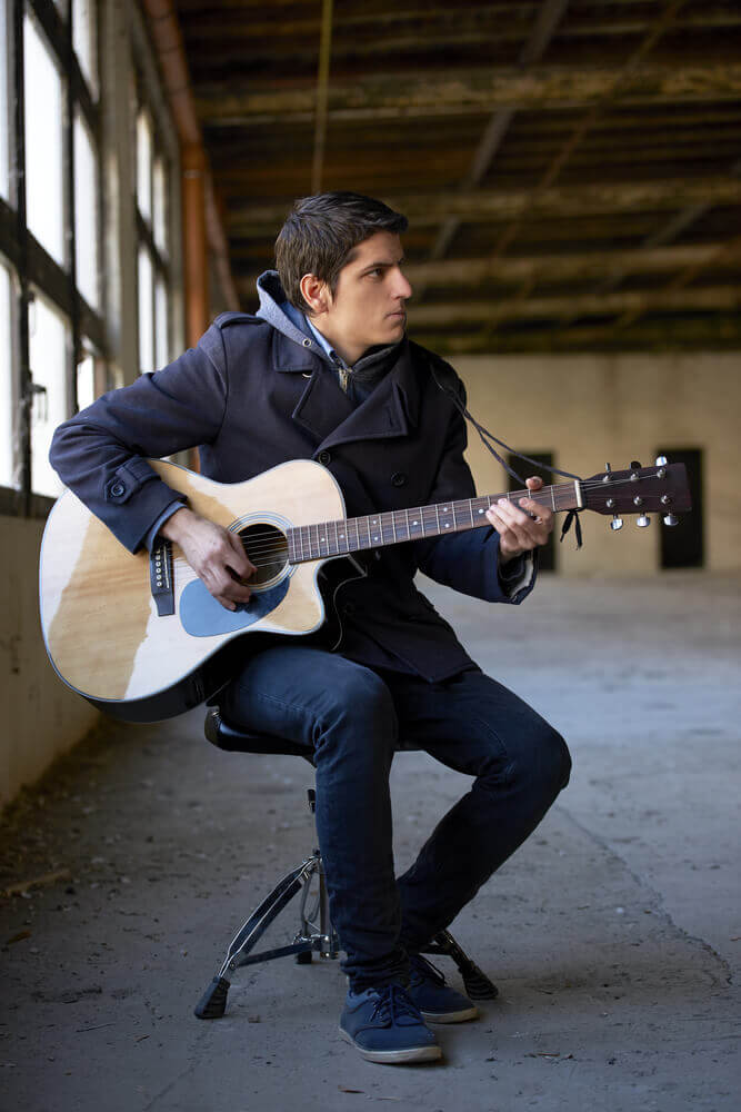 Full length shot of a young man playing acoustic guitar while sitting indoor