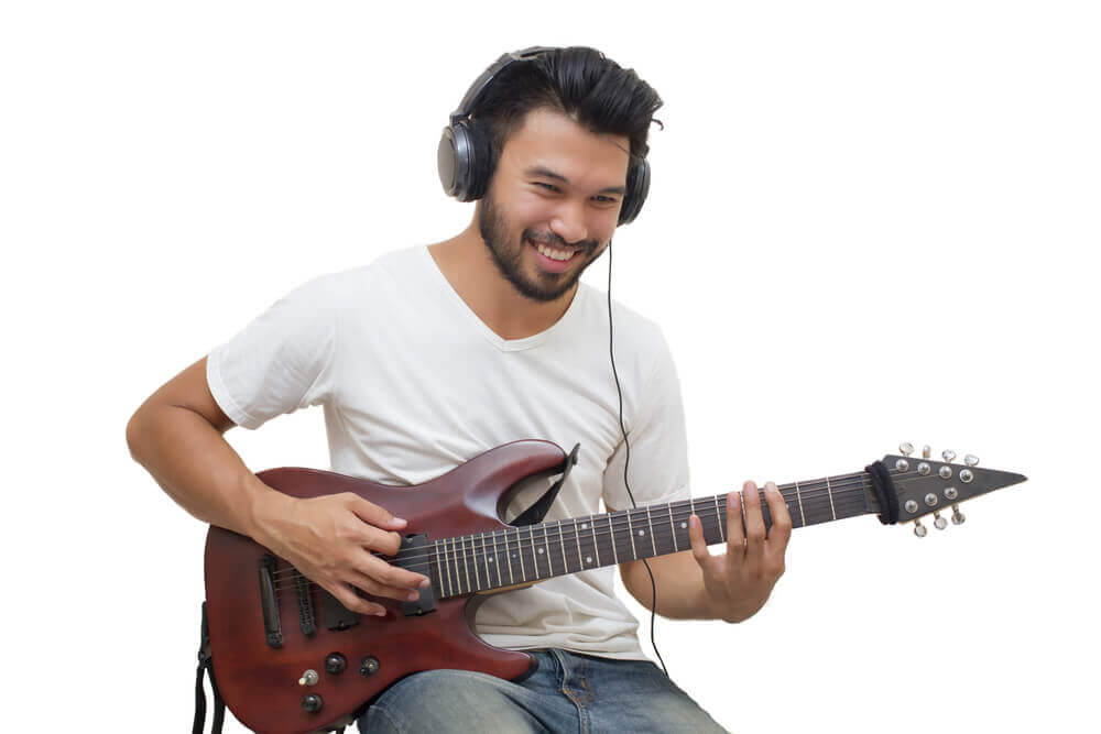 Handsome young asian man playing guitar and listen music with headphones