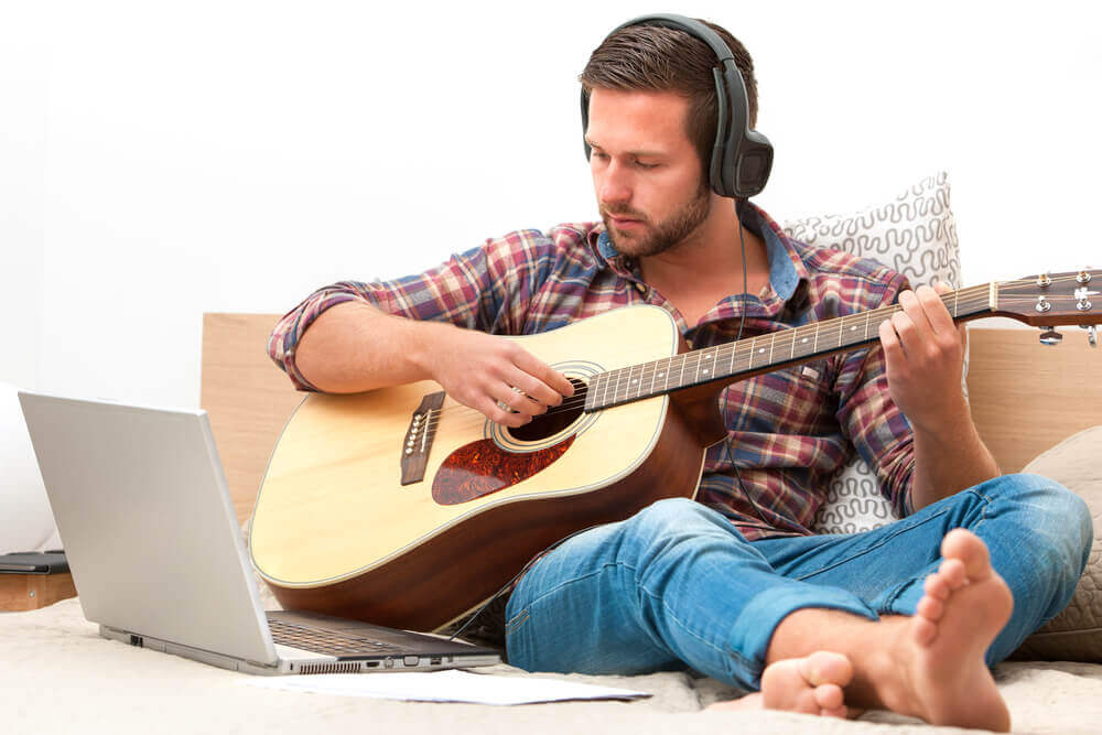 Man on sofa playing the guitar with laptop at home