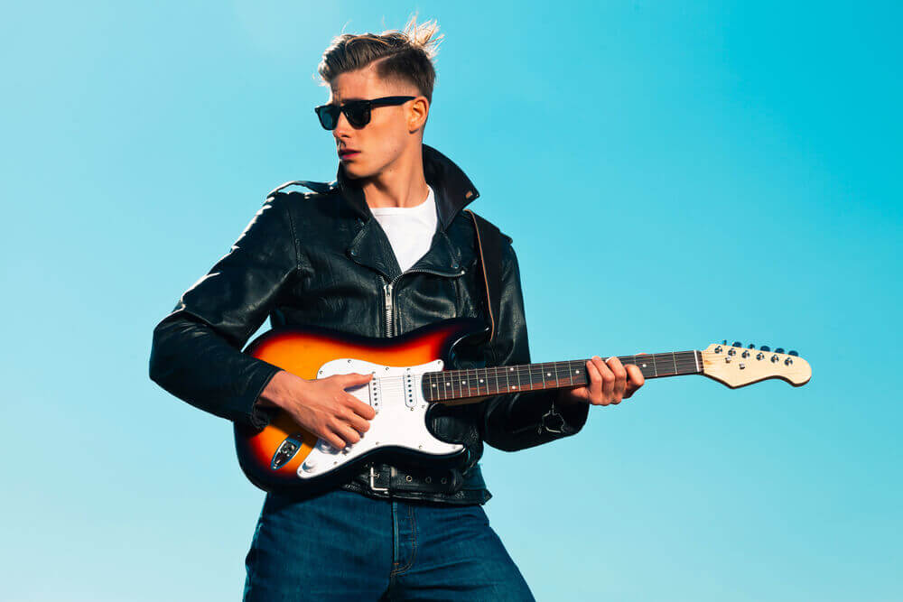 Retro fifties rockabilly electric guitar player wearing black leather jacket