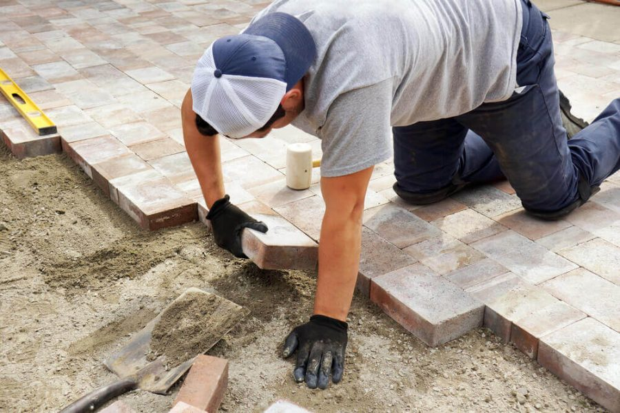 Worker setting paver bricks