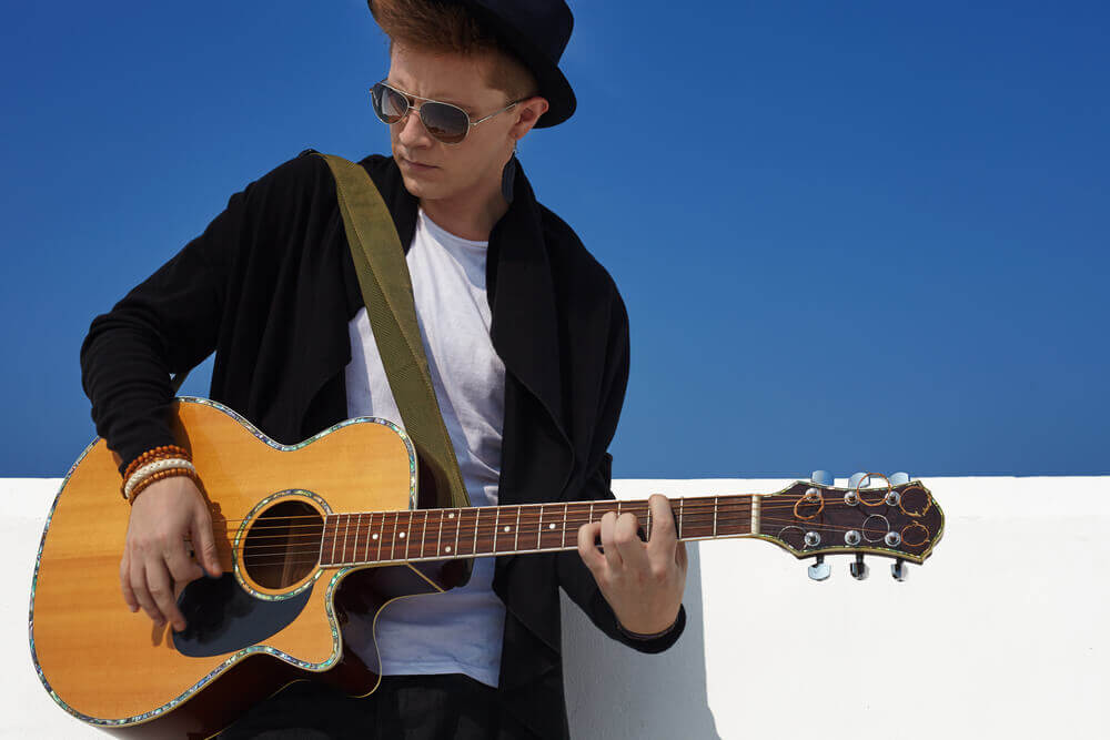 Young caucasian man in black clothes and hat playing on acoustic guitar