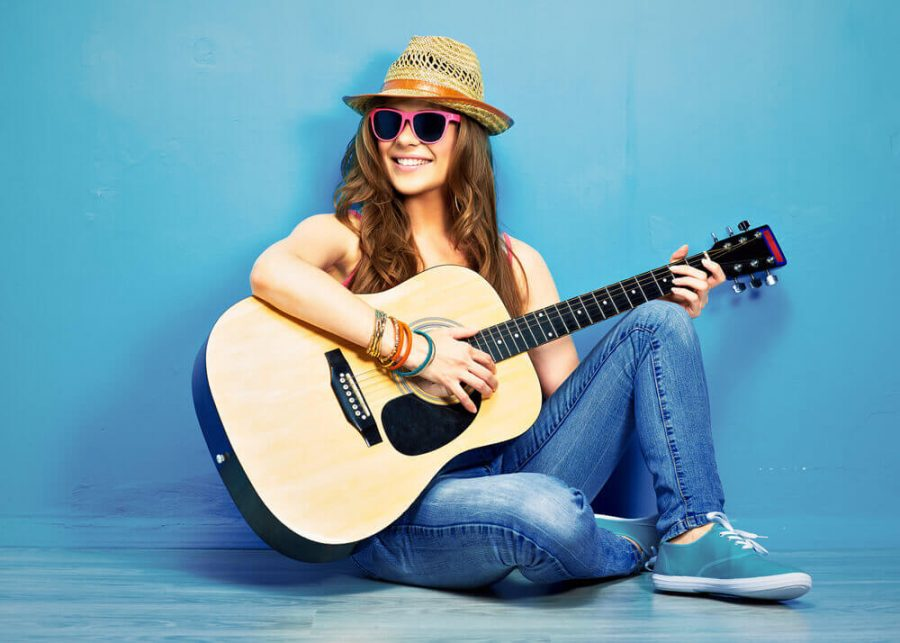 girl play music on acoustic guitar