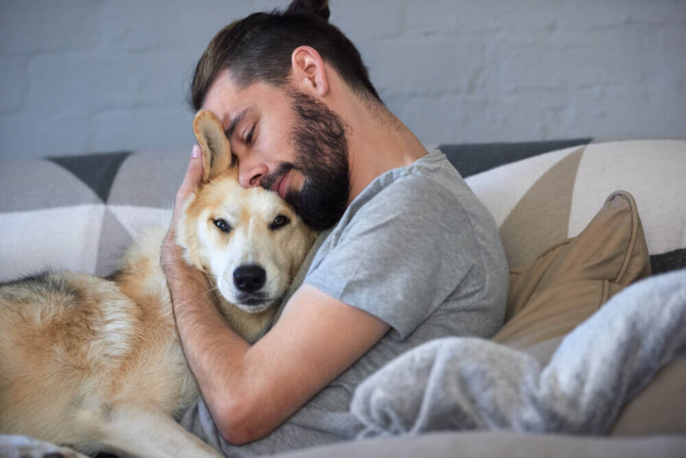 man snuggling and hugging his dog