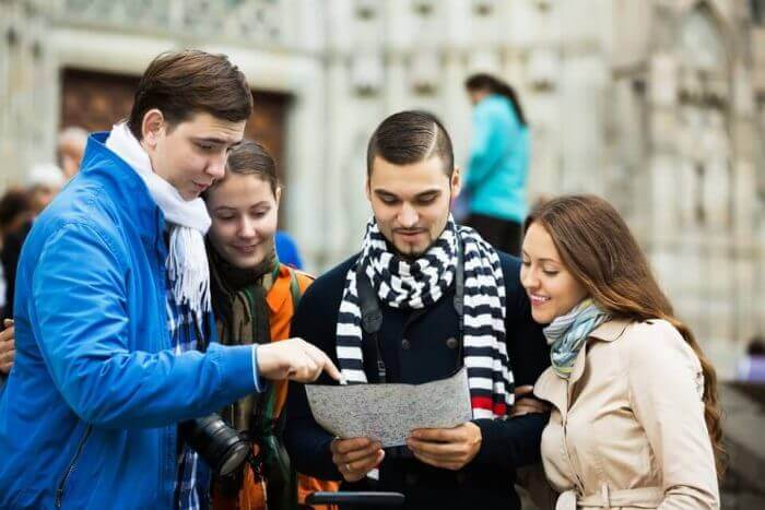 two happy couples of tourists reading city map